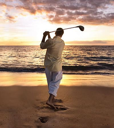 Golfer on Vancouver Island beach at sunset